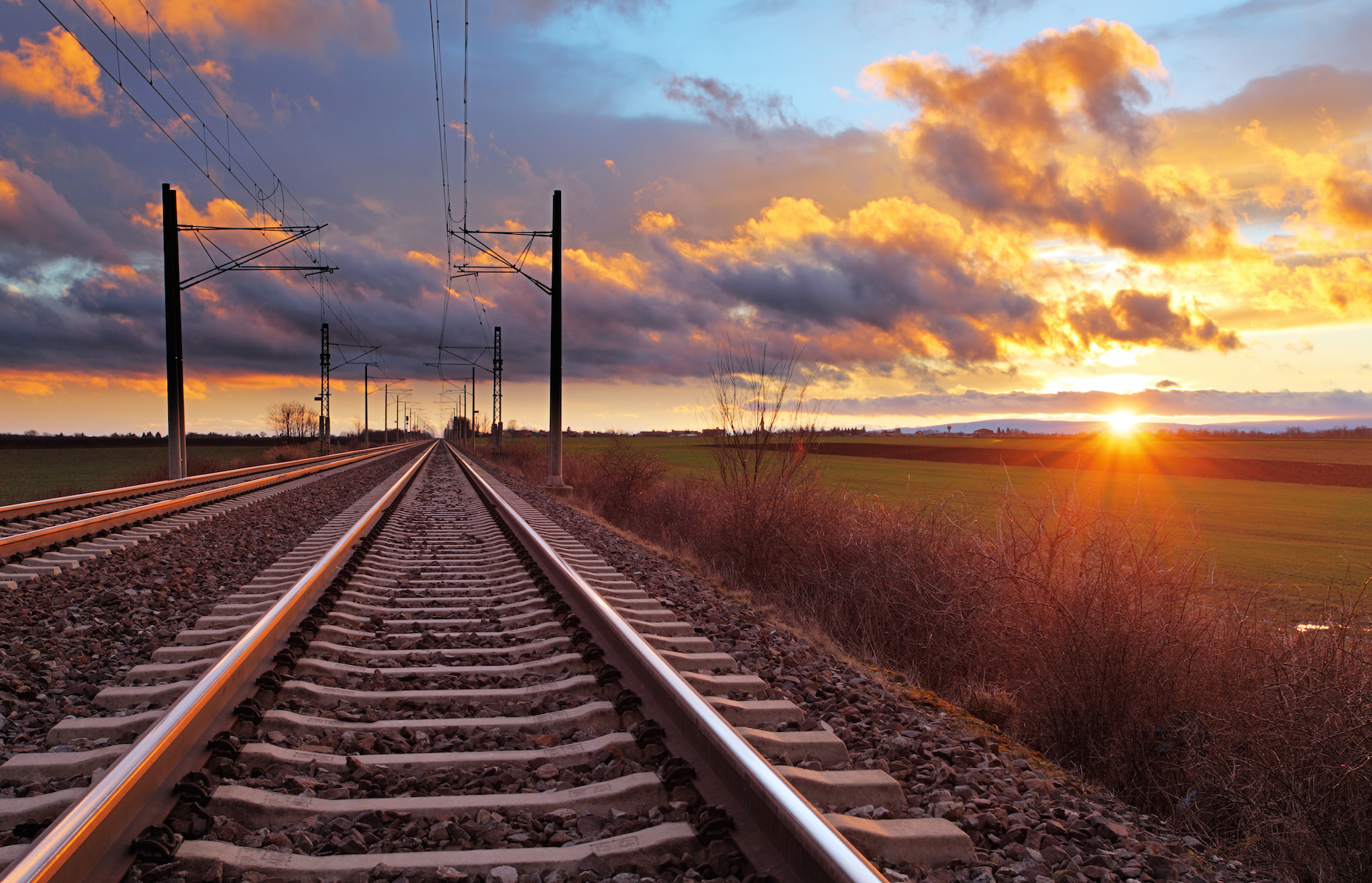 orange-sunset-in-low-clouds-over-railroad.jpeg